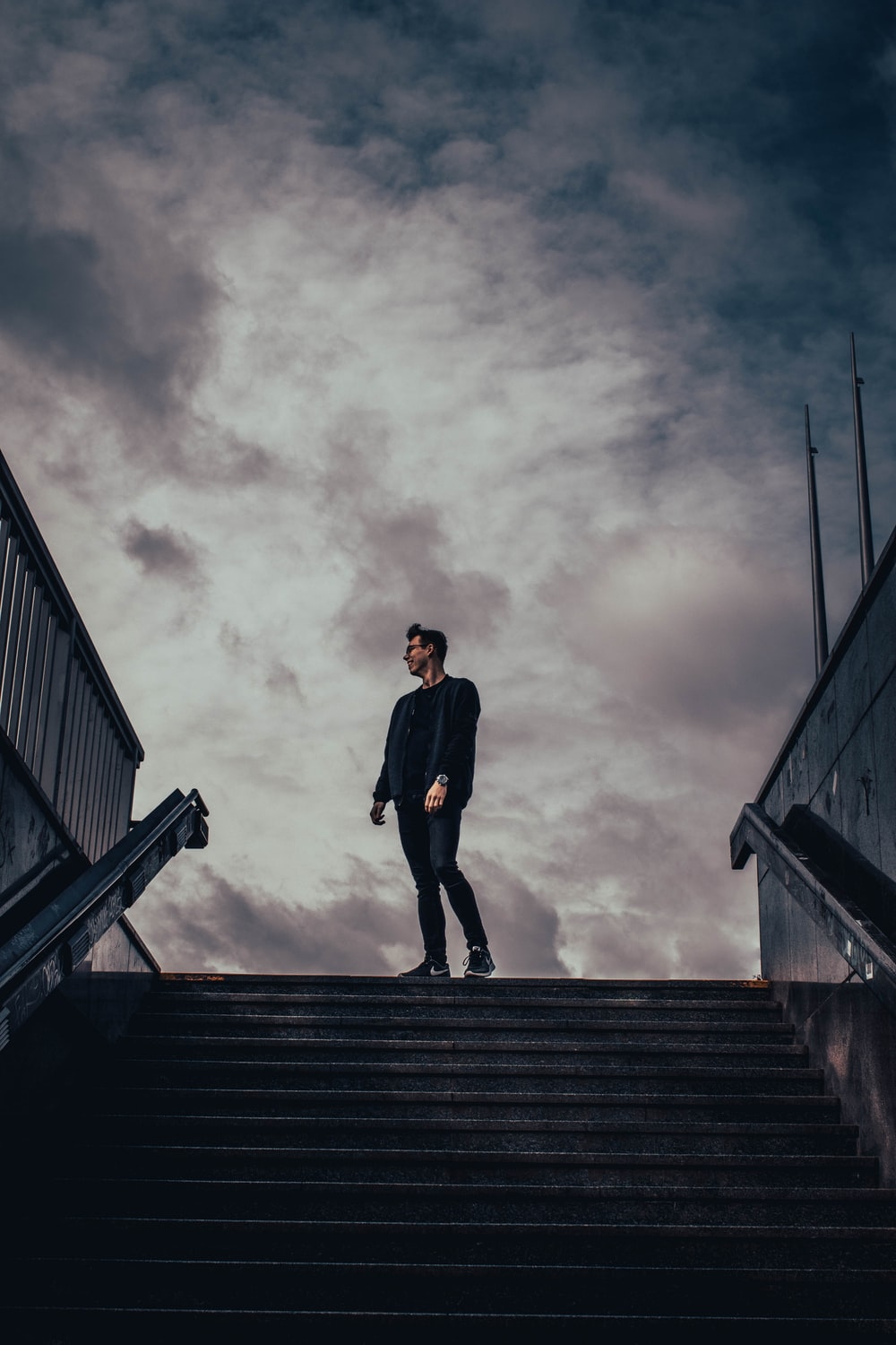 man standing beside staircase