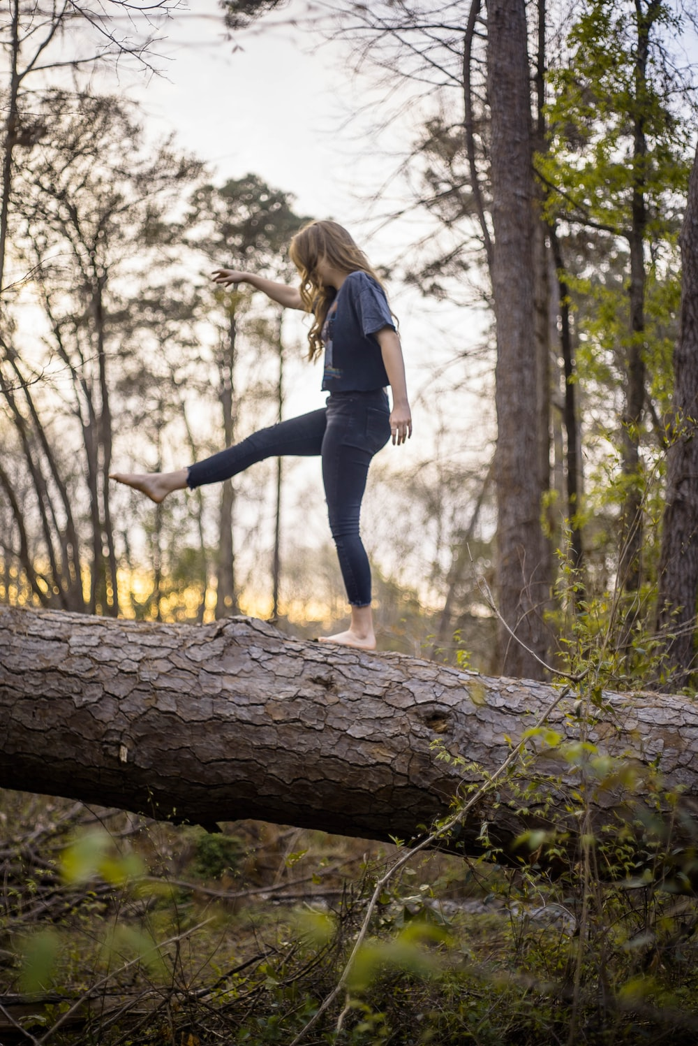 mujer en equilibrio sobre tronco