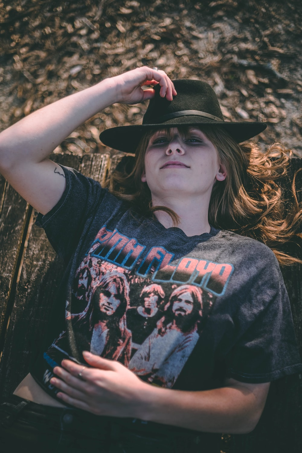 smiling woman in grey Pink Floyd shirt lying on brown wooden surface