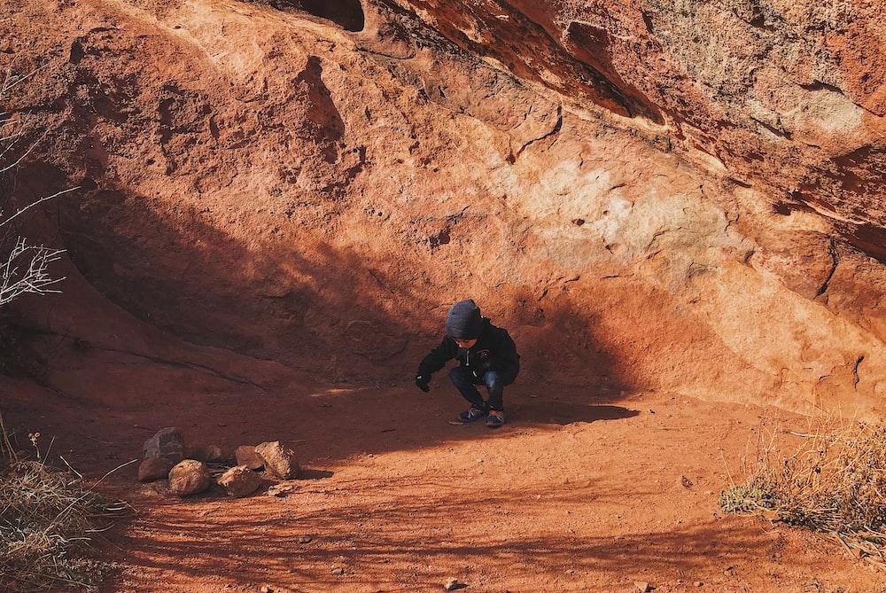 person wearing blue beanie across brown rocks