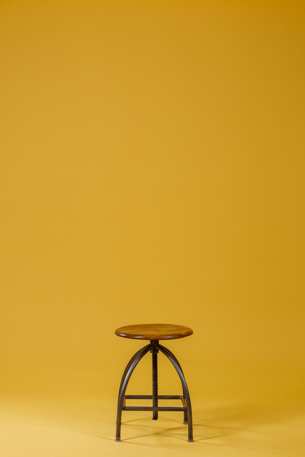 round brown wooden top and black base chair on yellow background