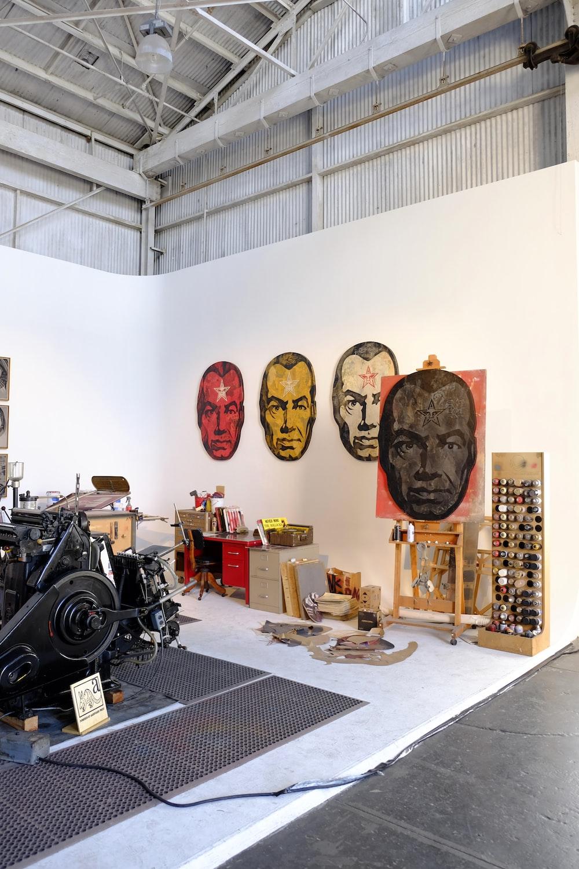 black engine near four man's head paintings