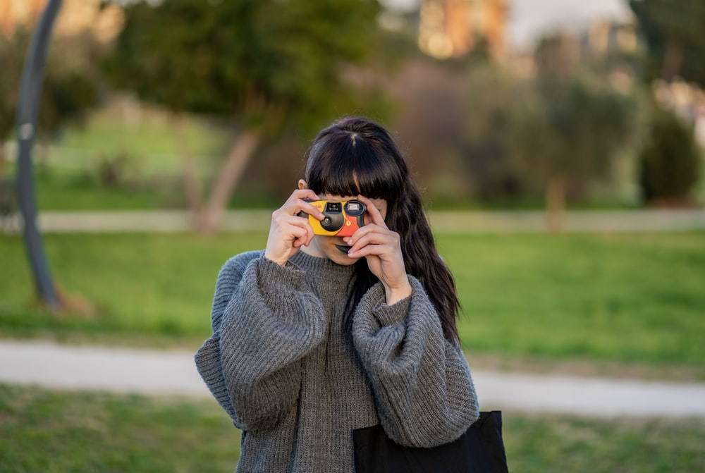 woman wearing gray knitted sweater holding yellow point-and-shoot camera