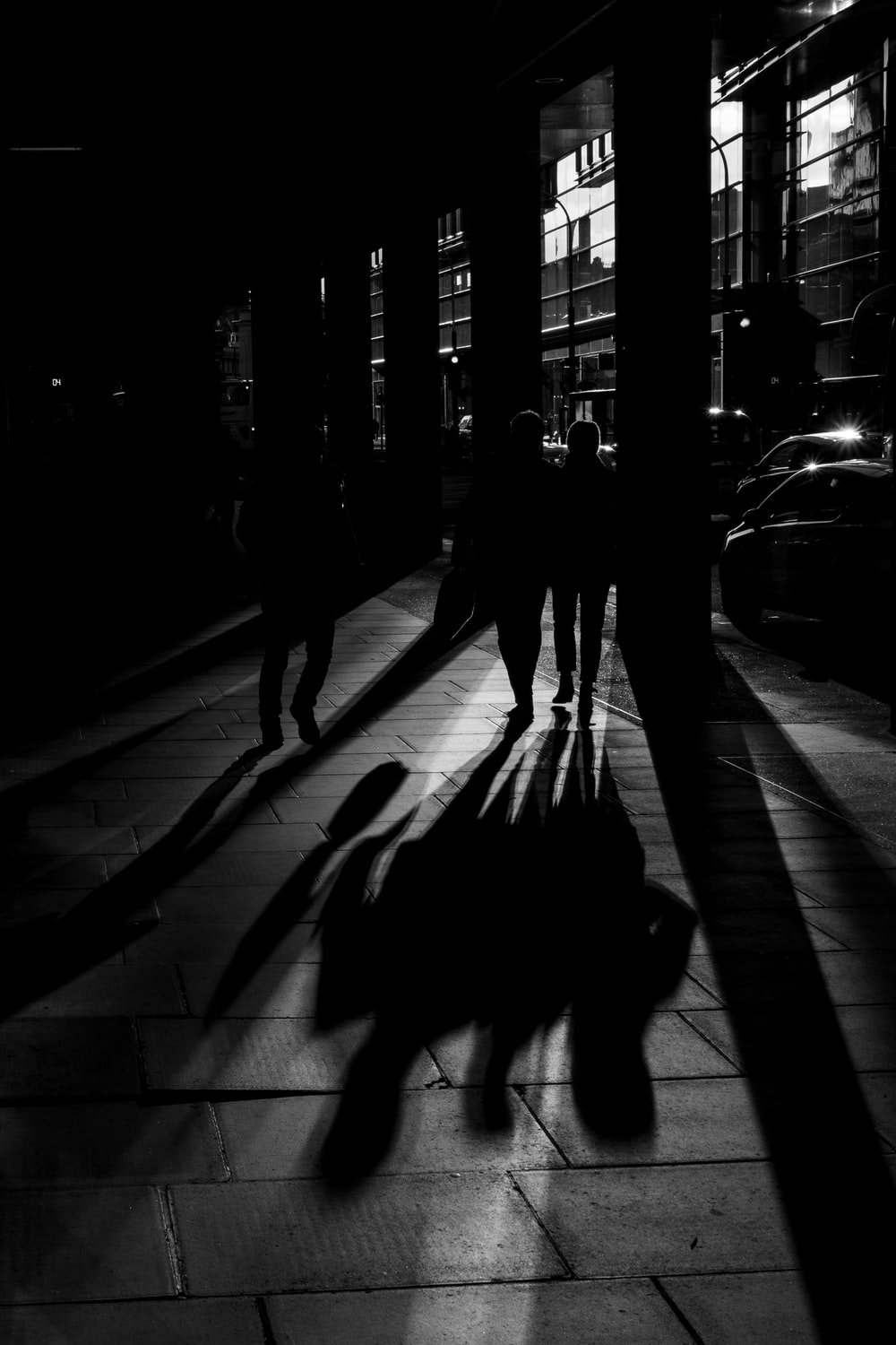 grayscale photography of people walking on pavement