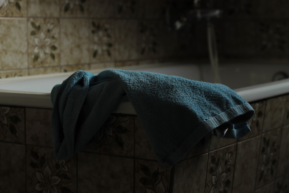 blue towel on bathtub edge
