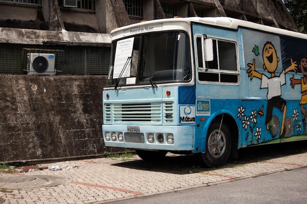 blue bus on sidewalk