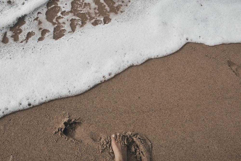 person's foot on sand near seashore