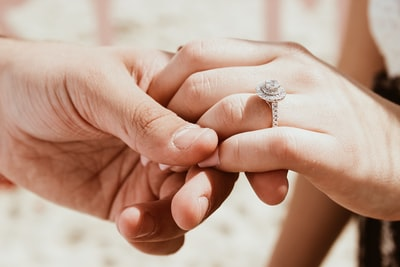 person holding another person's hand with ring ring zoom background