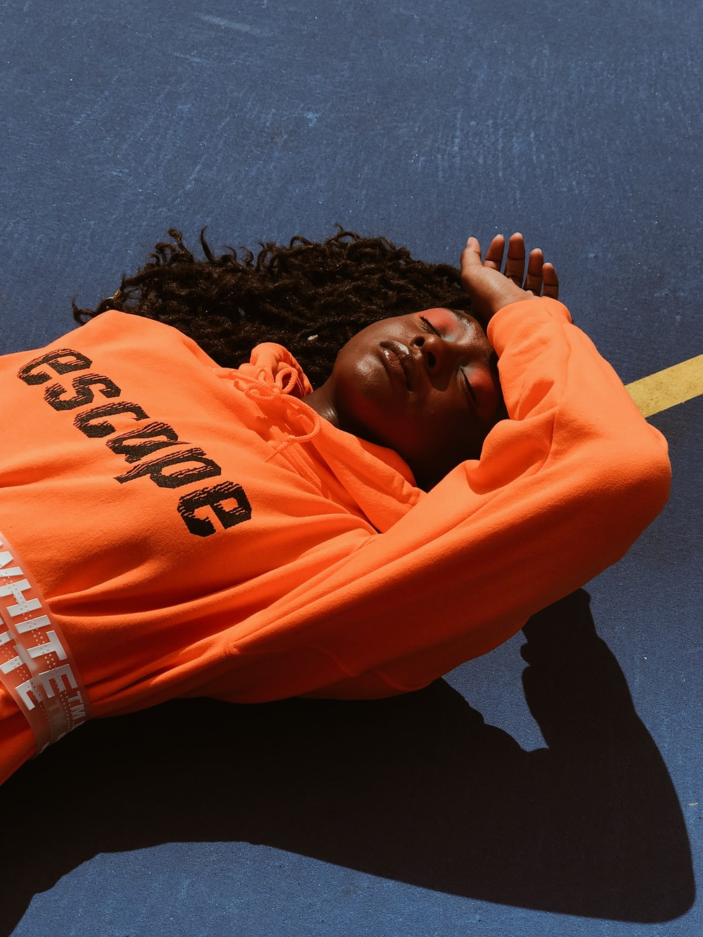 woman wearing orange pullover hoodie lying on road