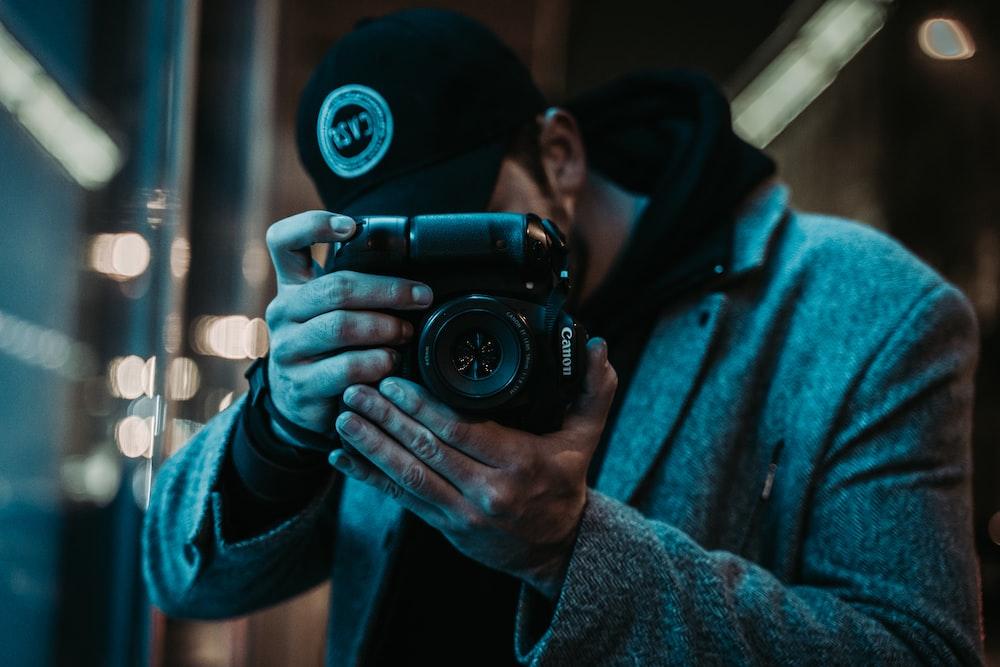 man in black cap holding camera