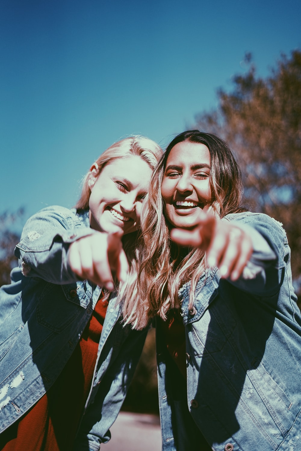 two women smiling while pointing fingers