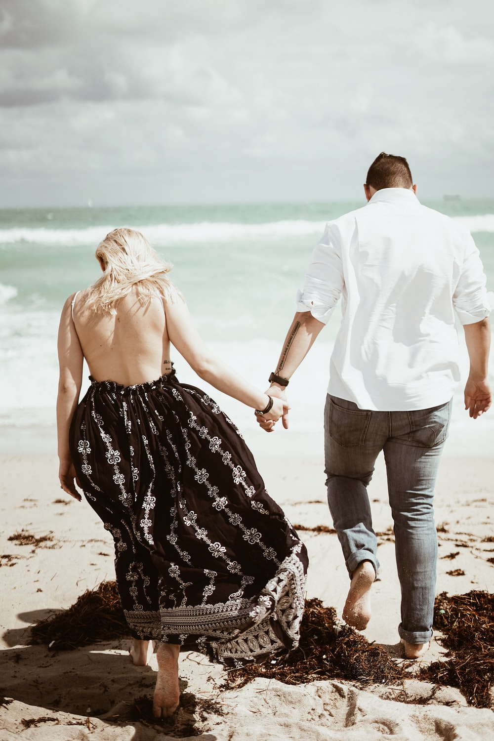 couple walking on sand near beach during daytime