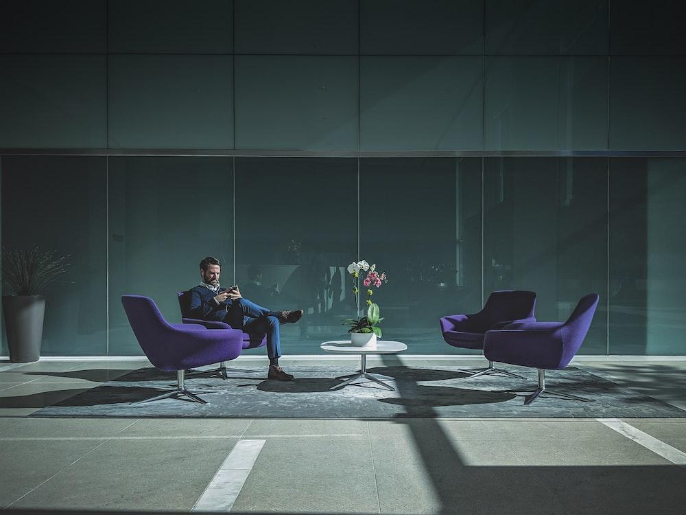 man sitting on purple cushion armchair