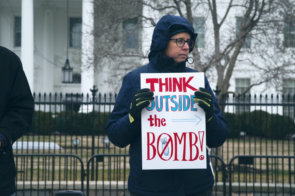 man holding think outside the bomb signage during daytime