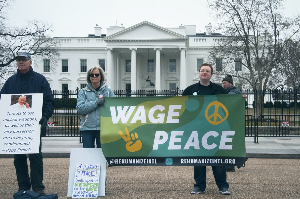 people holding Wage Peace signage in front of white concrete building during daytime