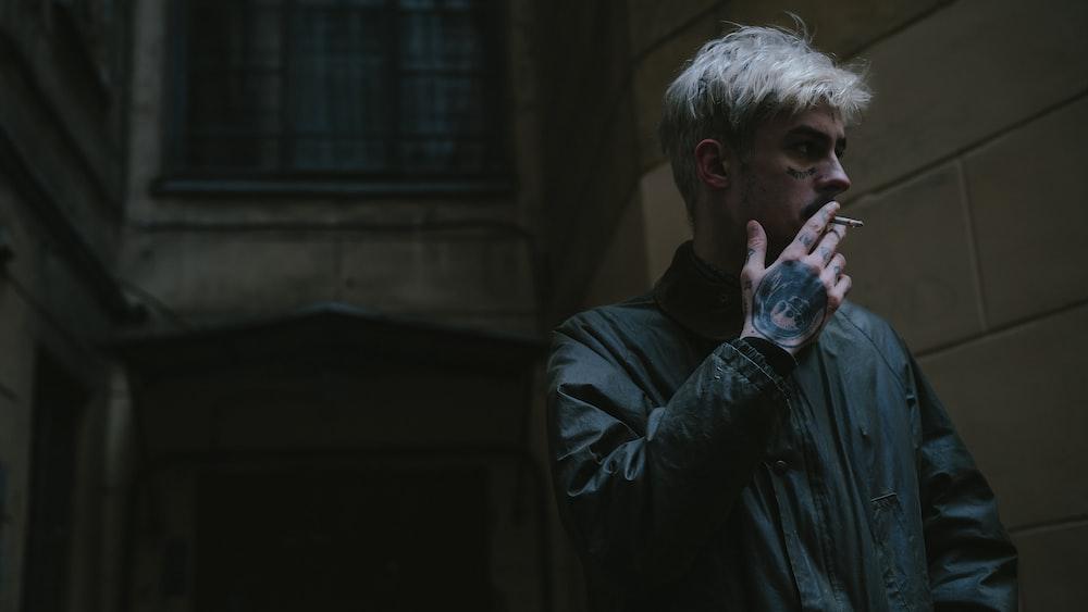 man in black jacket smoking