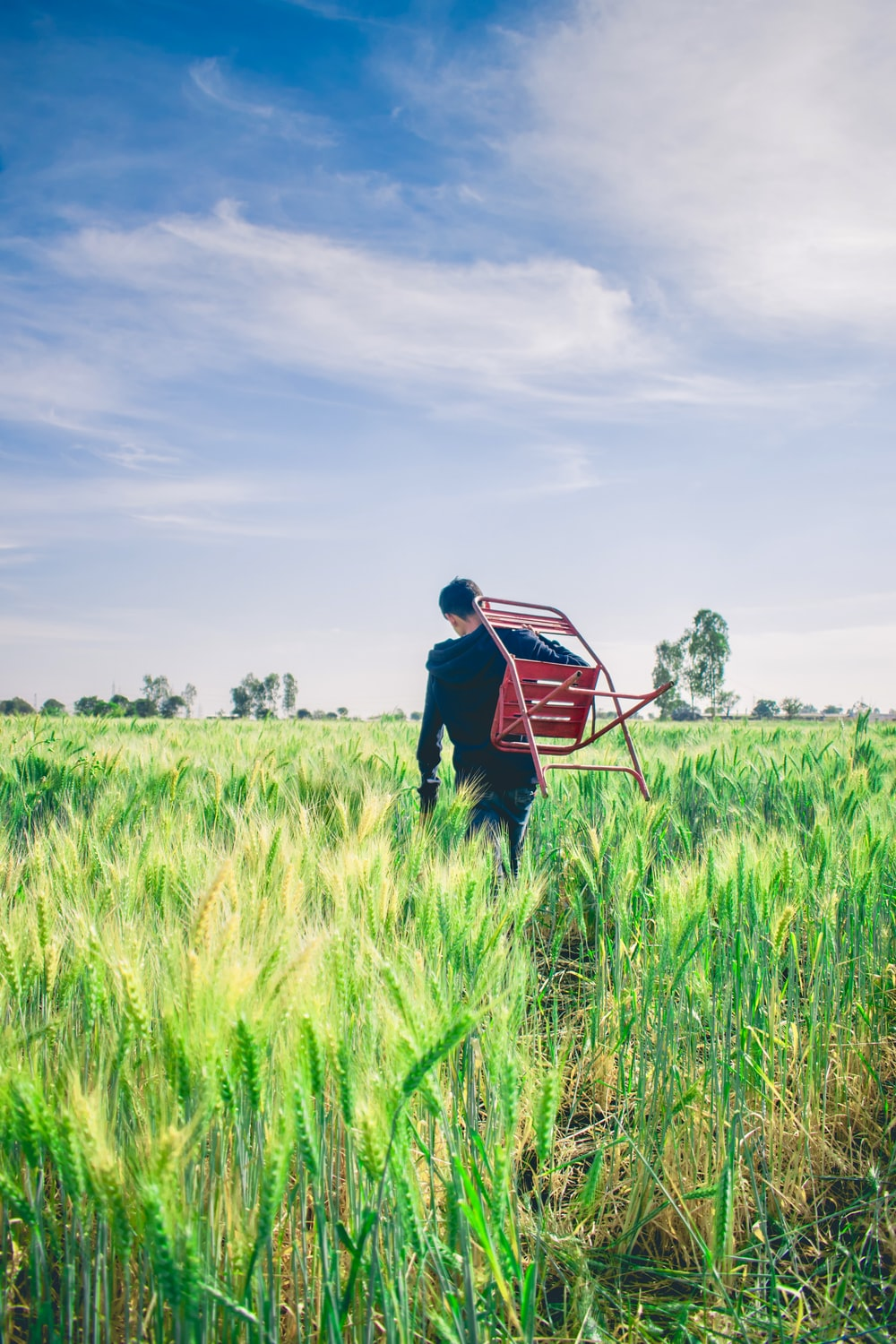 man in black sweater carrying chair in middle of field