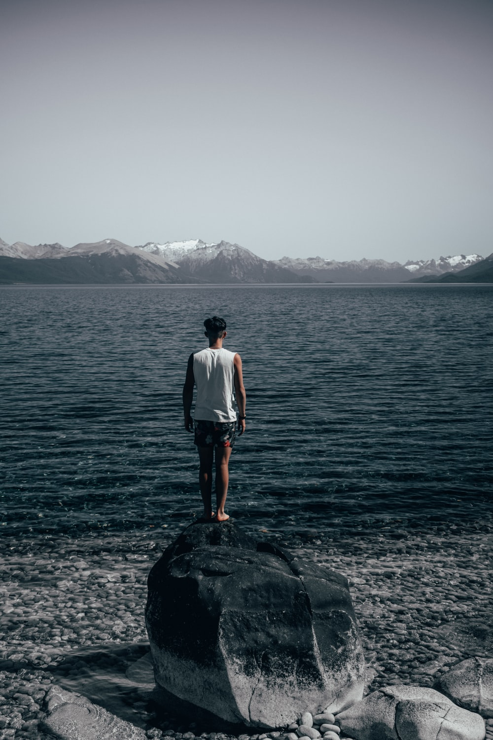 man standing on rocks looking at rippling water