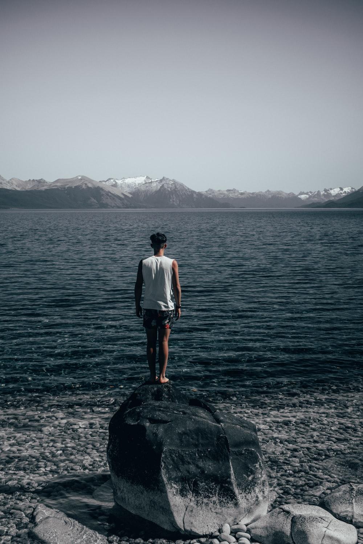 man standing on rocks looking at rippling water