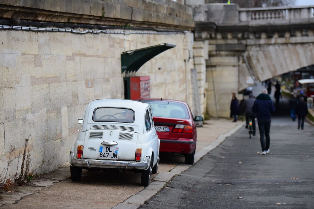 two white and red cars parked near wall