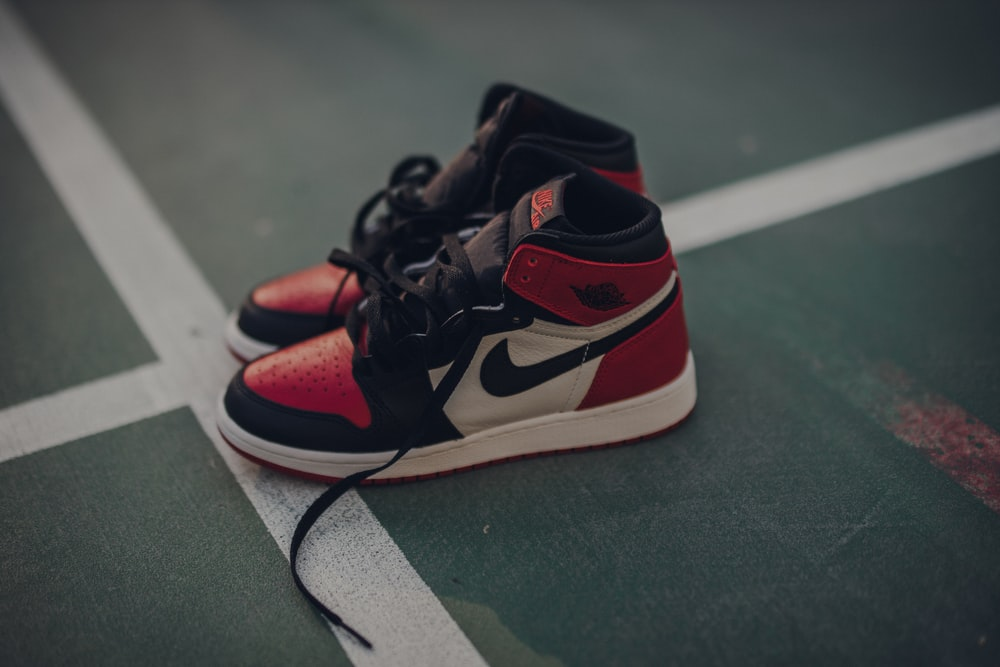 pair of white black and red Nike sneakers on floor