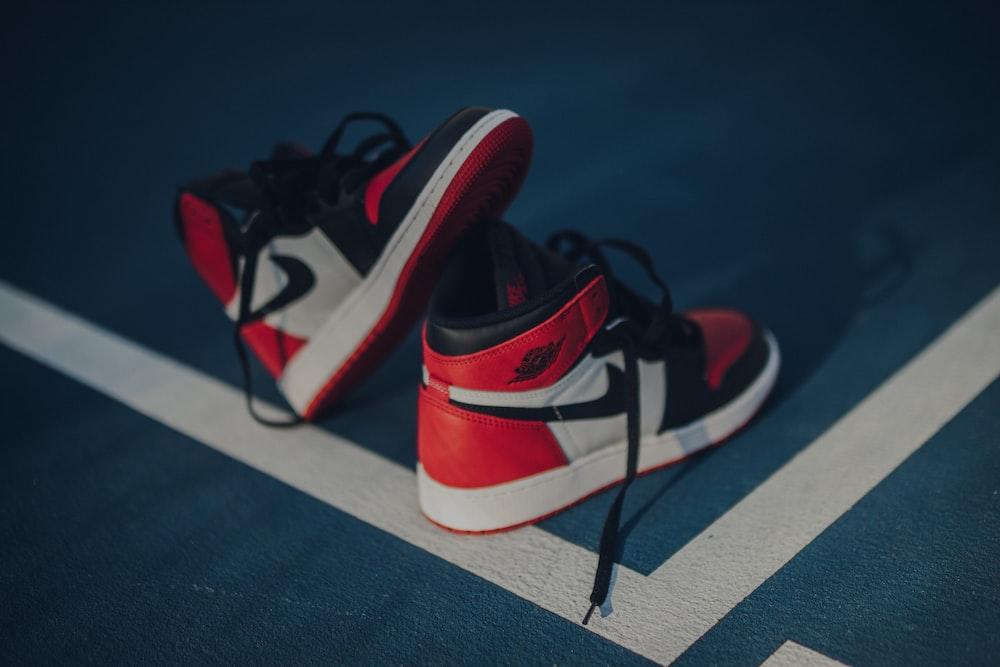 pair of white-red-and-black Nike Air Jordan 1 shoes on floor