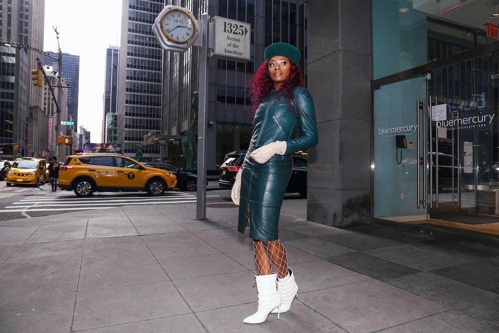 woman in gray leather dress standing on sidewalk