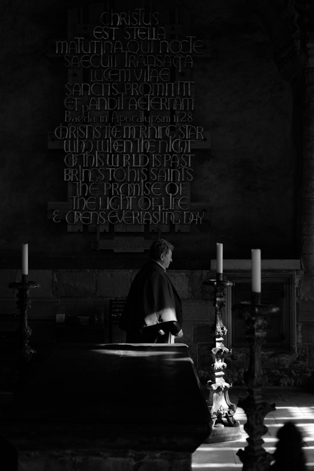 grayscale photography of man standing near candle holder