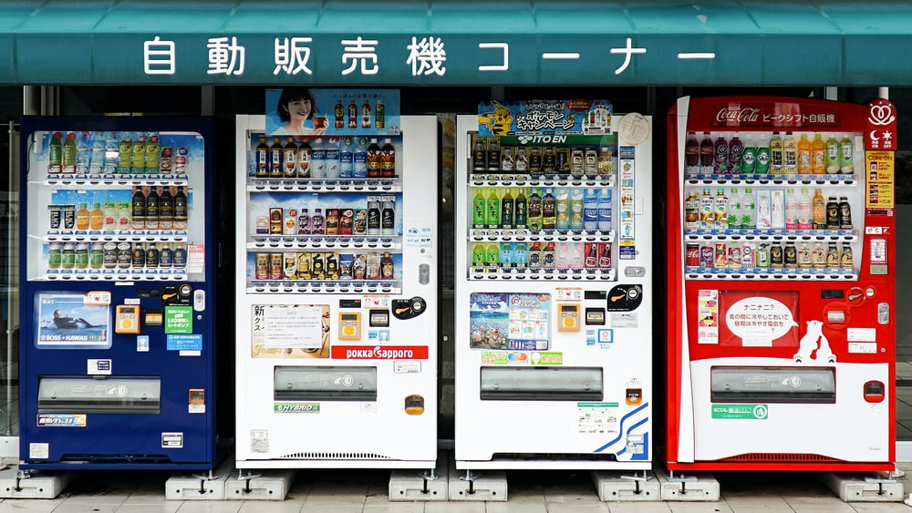 four white, red, and blue vending machines