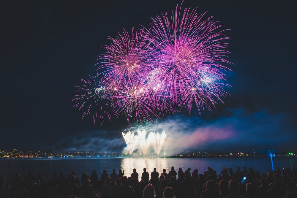 crowded people watching fireworks at night