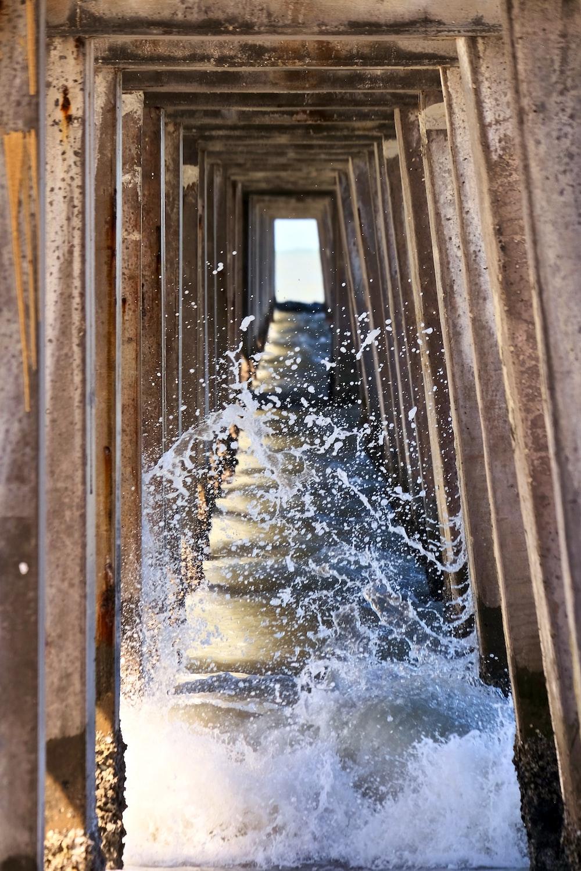 waves under brown wooden bridge