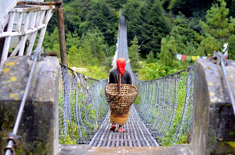 person walking at bridge while carrying brown basket
