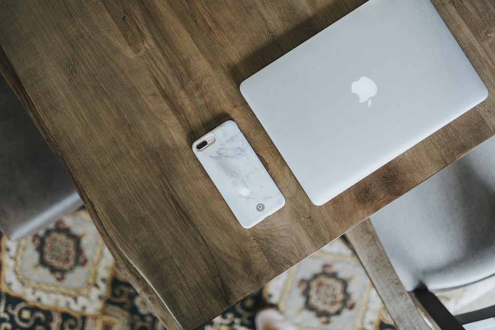 MacBook silver and silver iPhone case on top of brown wooden table