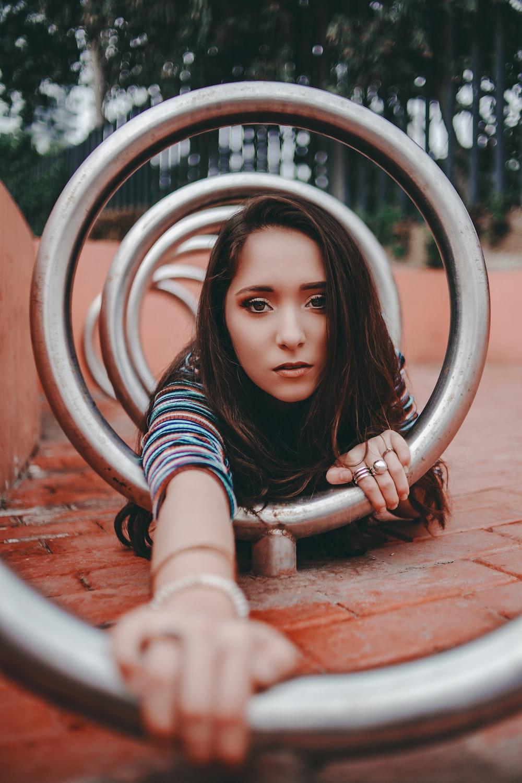 woman crawling on round gray metal bar