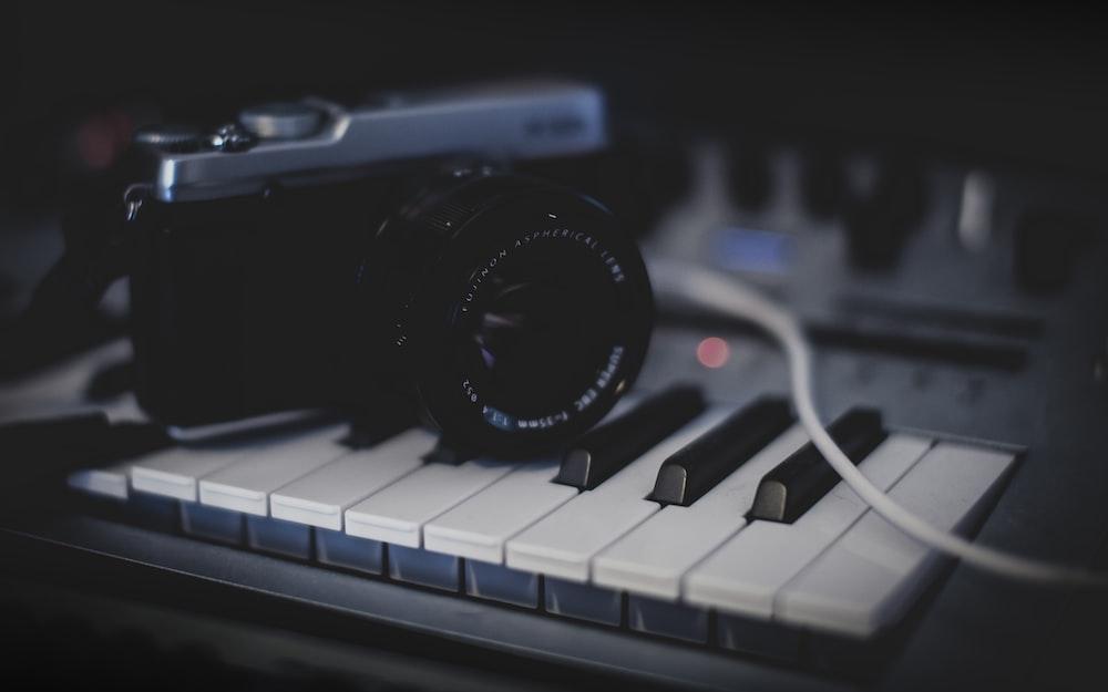 black and gray SLR camera on keyboard