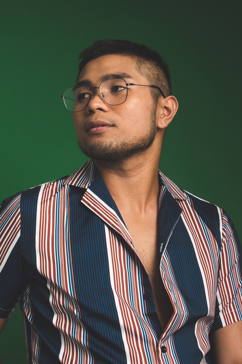 man in button-up T-shirt and eyeglasses