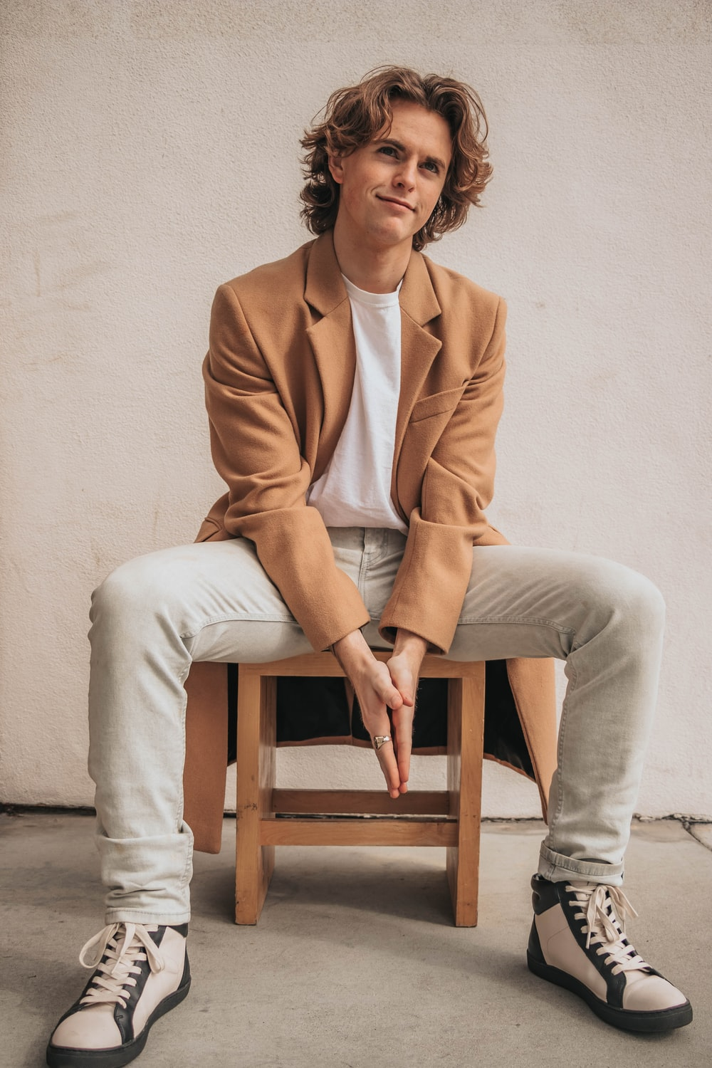 man sitting on a wooden chair