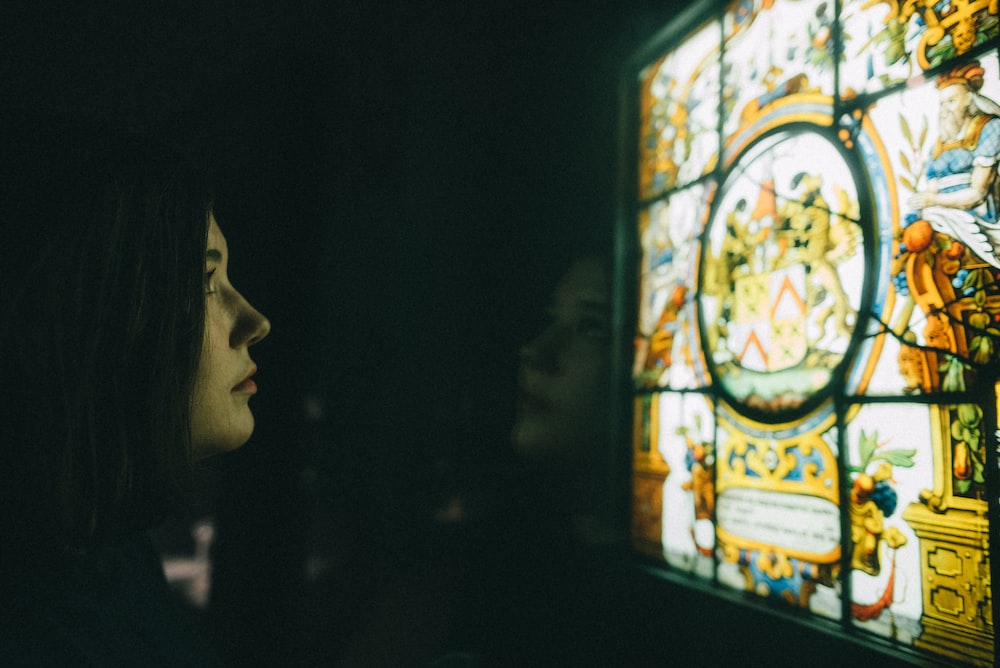woman facing on multicolored stained glass