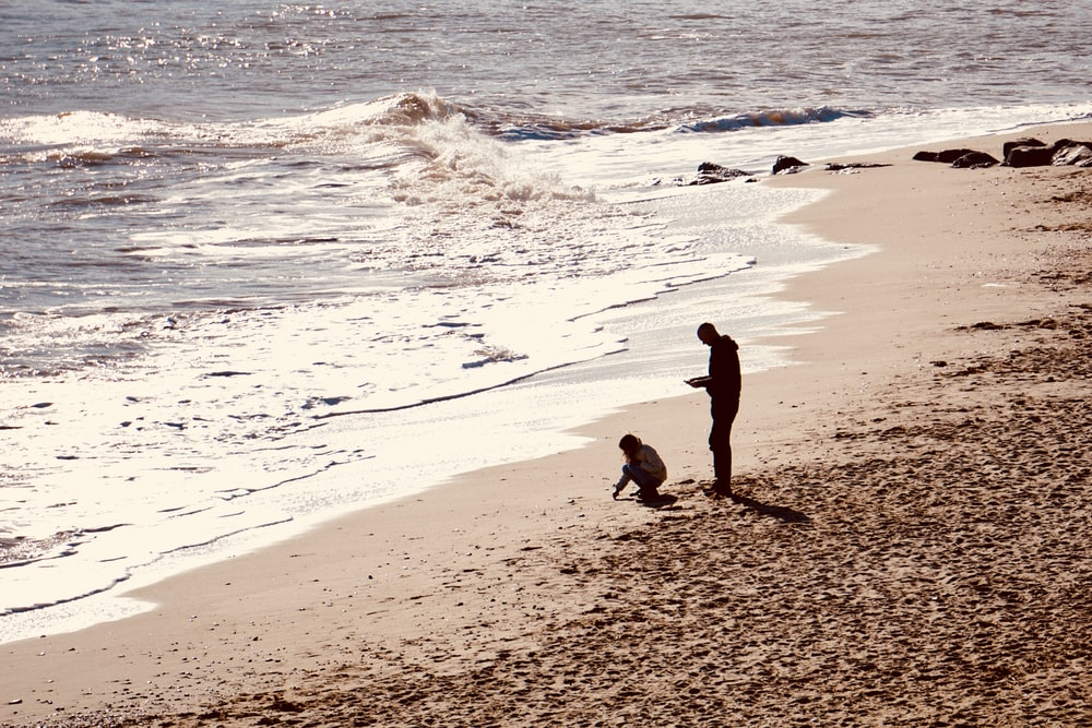 two person standing in beach during daytime
