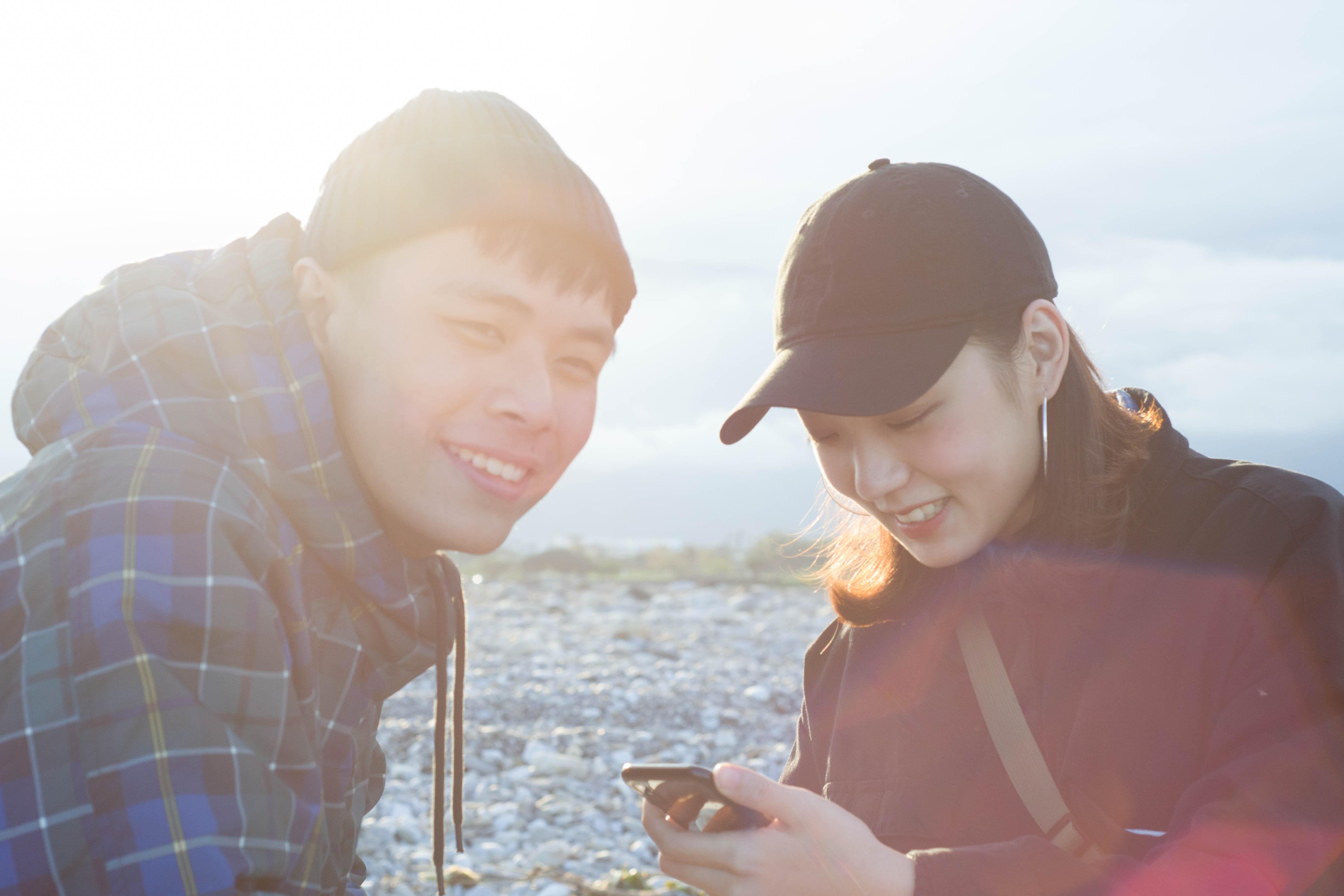 man sitting beside woman using smartphone