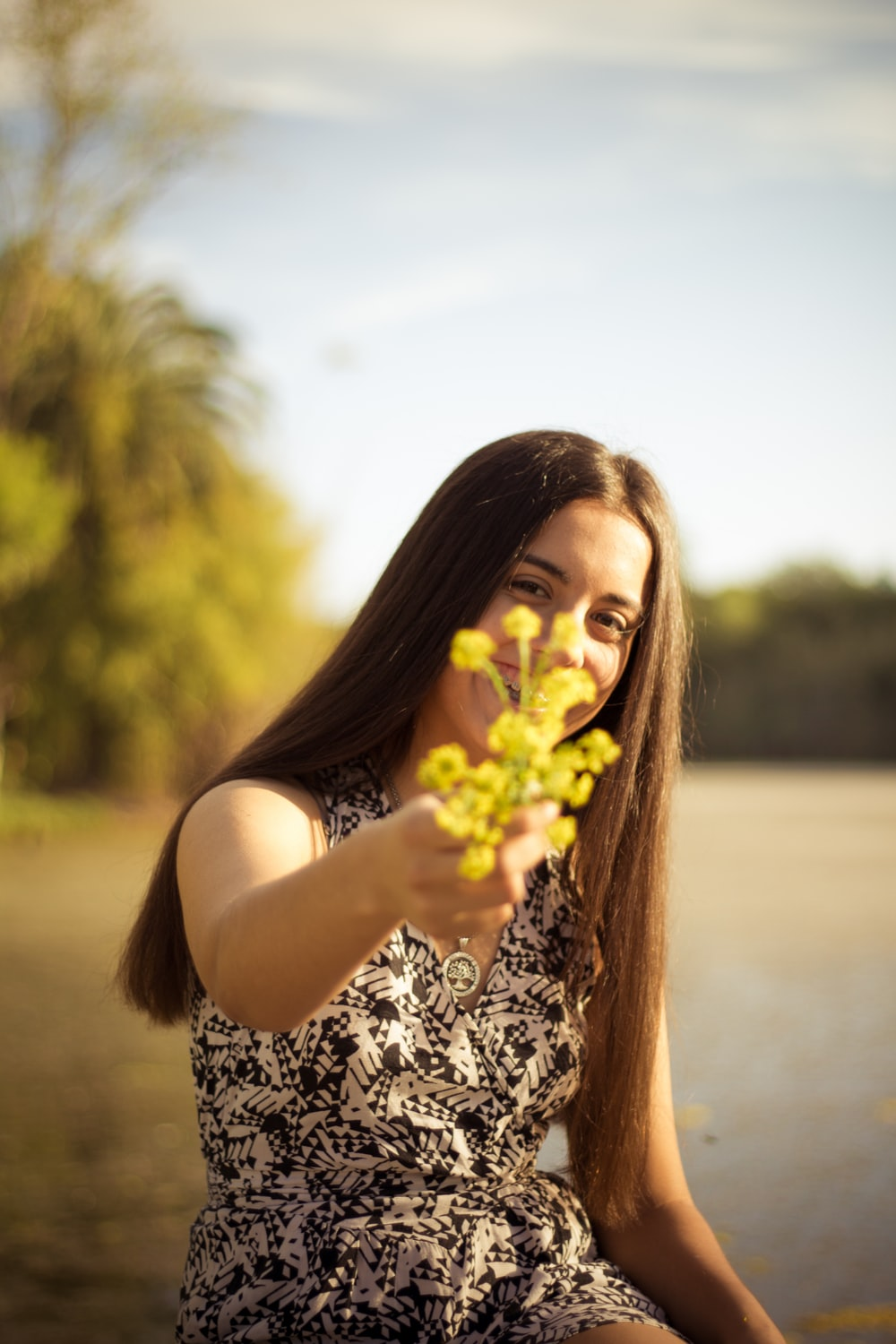 woman holding yellow flower during daytime