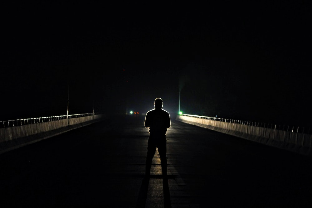 silhouette of man standing in the middle of asphalt road