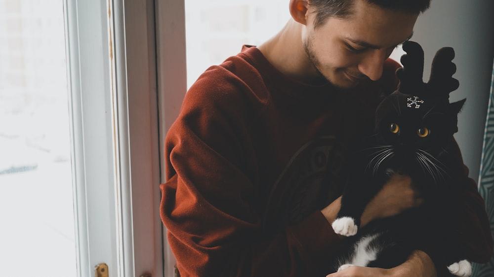man holding cat near door