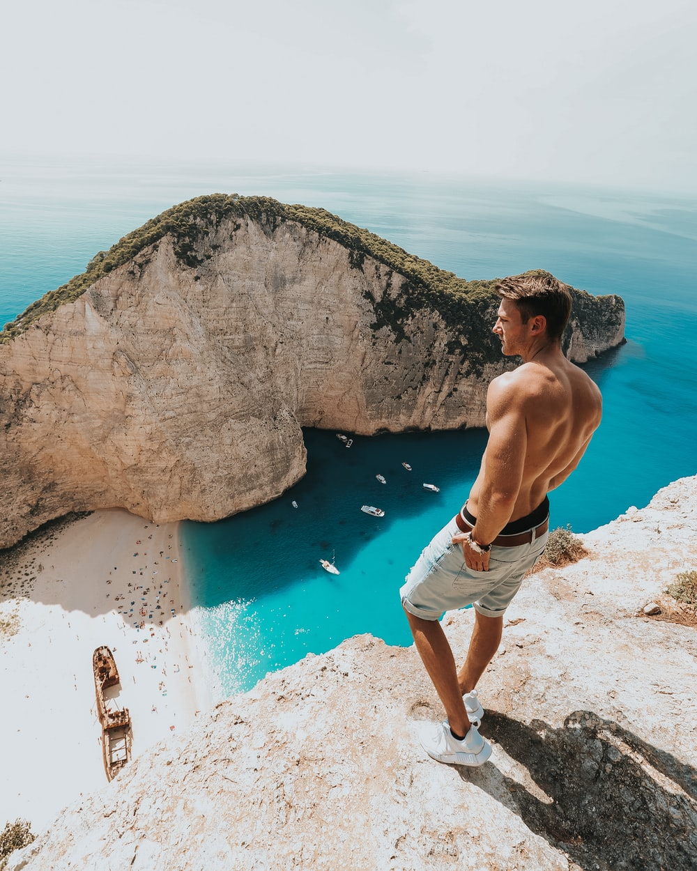 man standing on rock near body of water during daytime