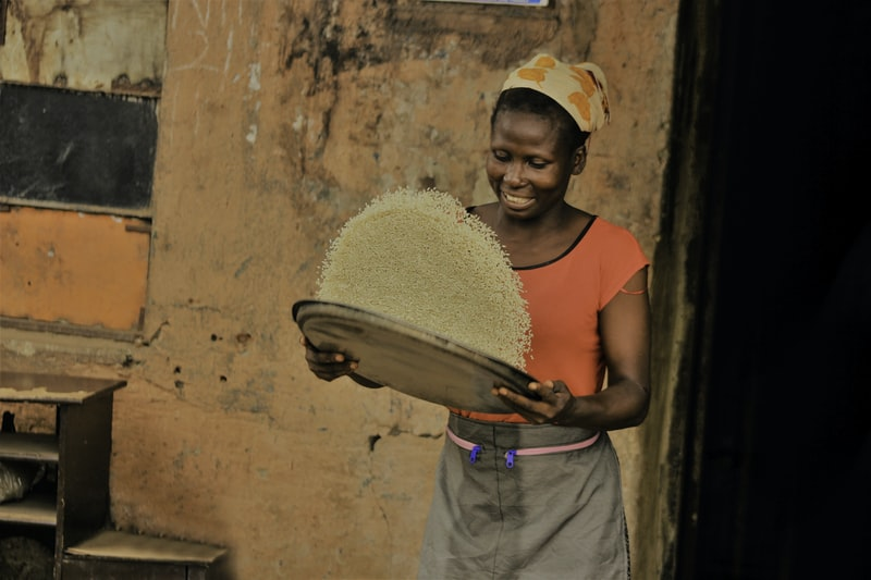 woman holding basket of rice