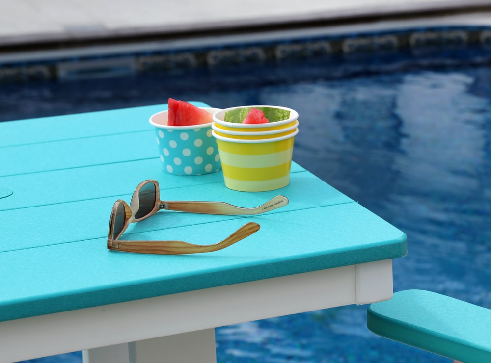sunglasses beside cups on table near pool