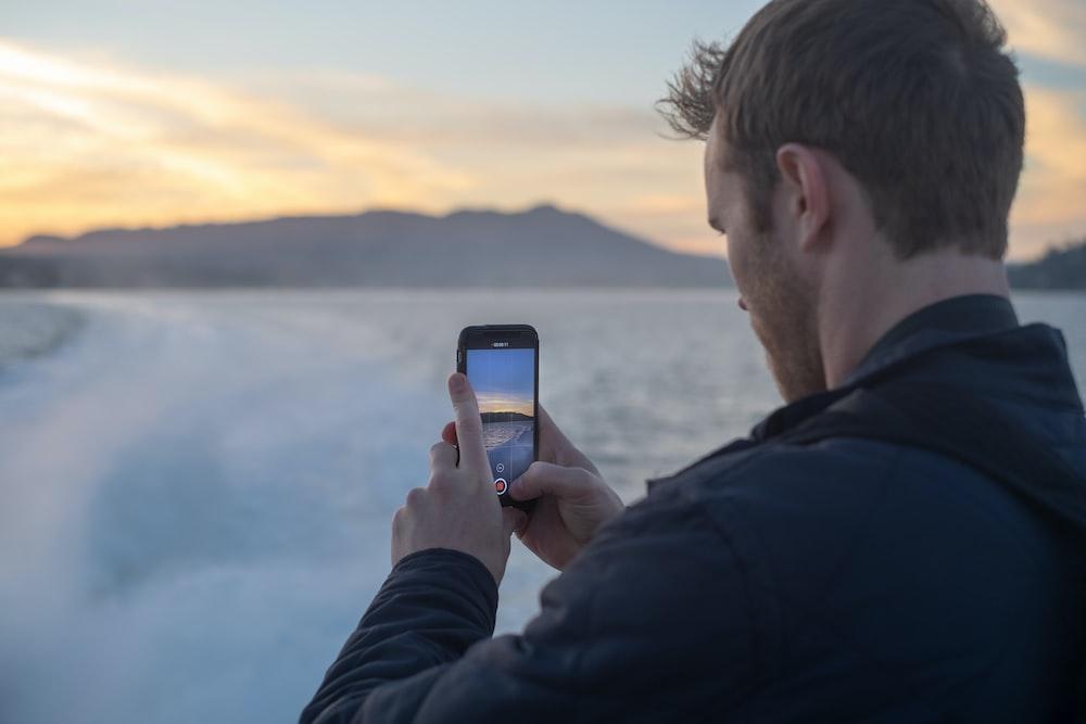 man taking photo of snow covered lake during sunrise