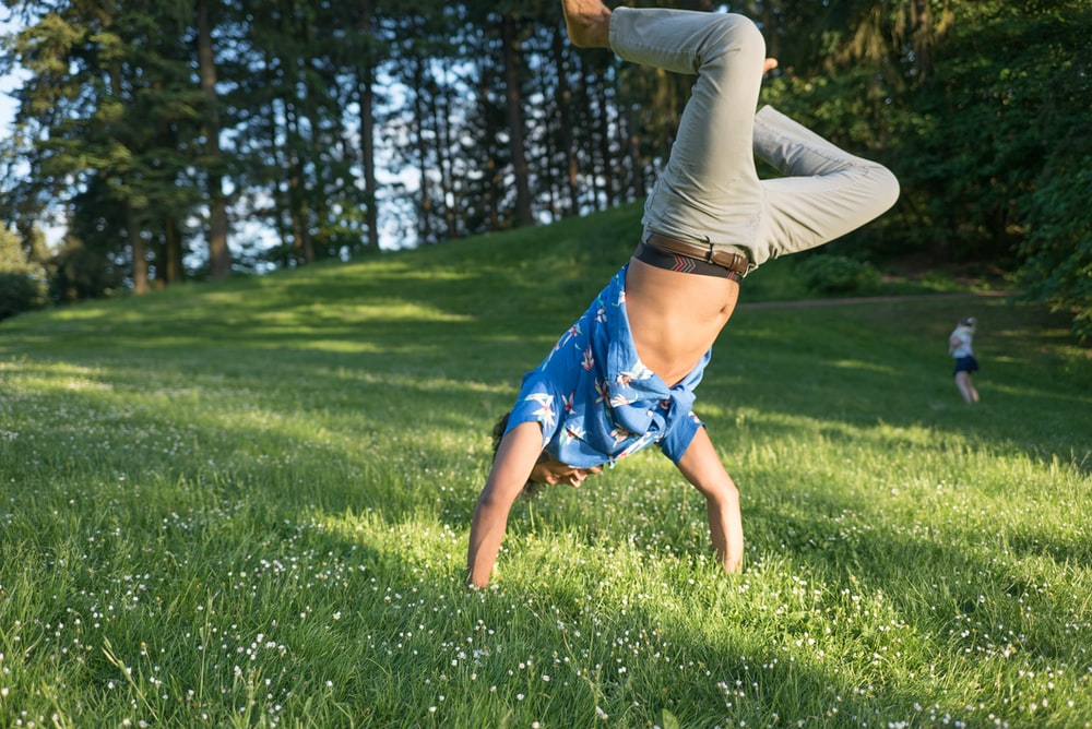man in blue shirt and jeans standing upside down in grass field