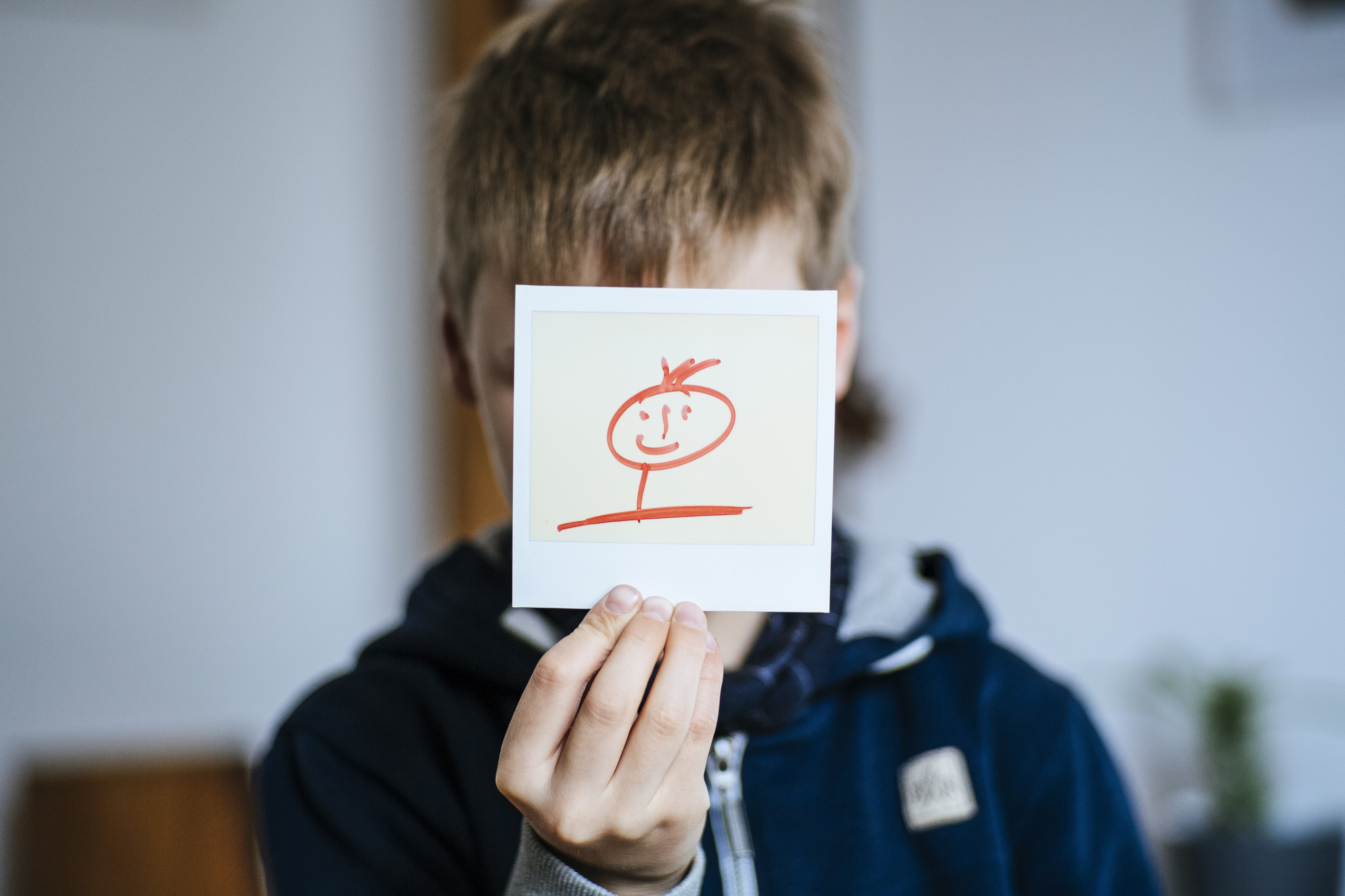 boy holds white card with drawing