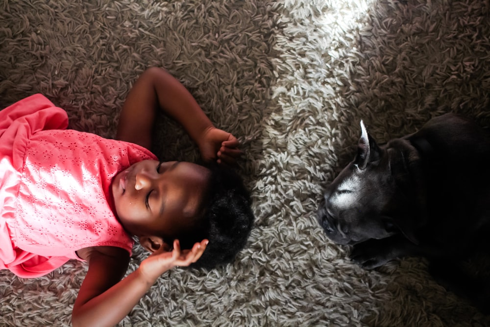 girl laying on rug beside black-short coated animal